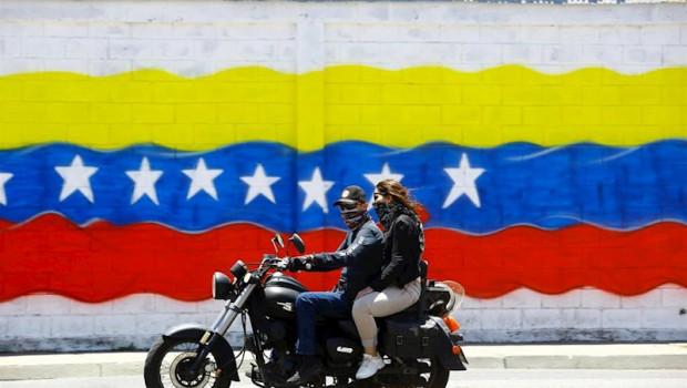 ep jovenes con mascarilla frente a una bandera de venezuela